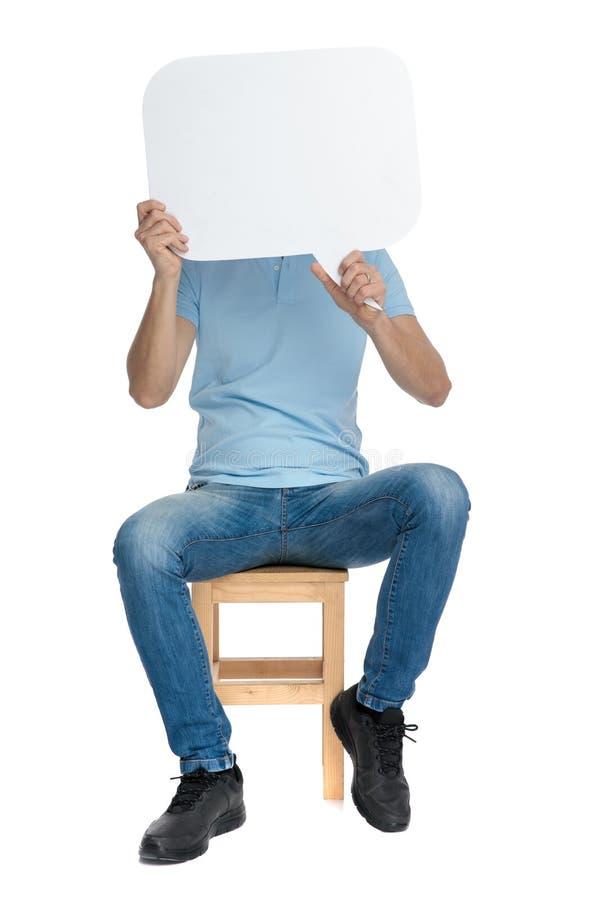 Homem ocasional que cobre sua cara com um discurso vazio fotos de stock royalty free