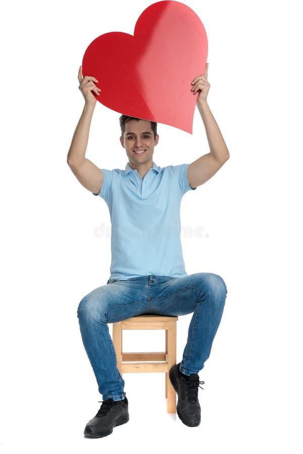 Homem ocasional que guarda uma forma do coração acima de sua cabeça fotos de stock