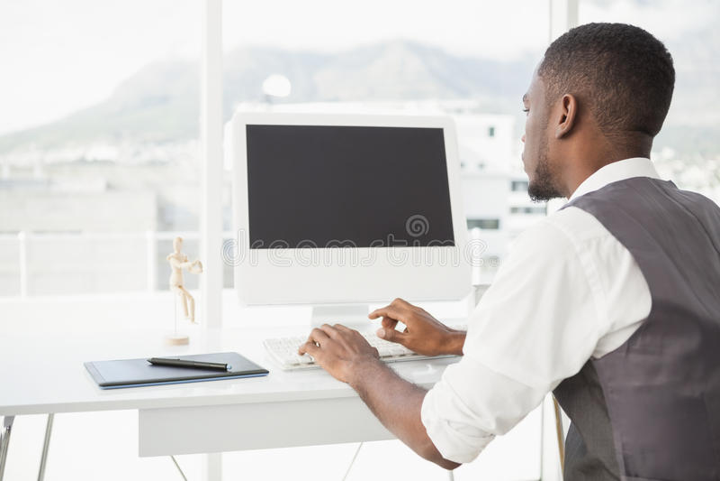 Homem ocasional que trabalha na mesa com computador e digitador fotografia de stock