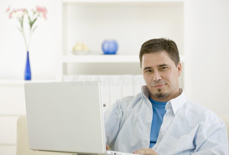 Homem ocasional que usa o portátil imagem de stock royalty free