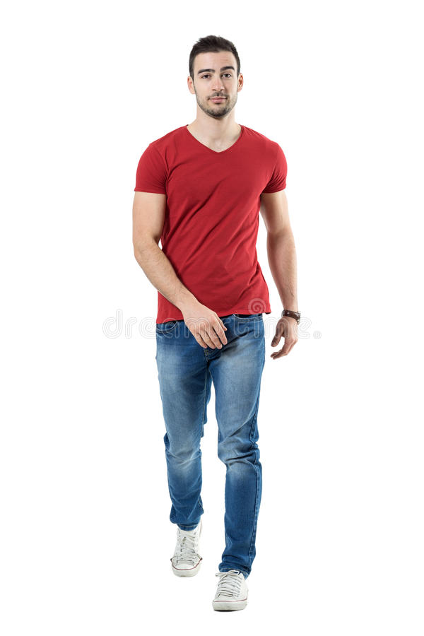Homem ocasional relaxado nas calças de brim e no t-shirt vermelho que anda e que olha a câmera imagens de stock royalty free