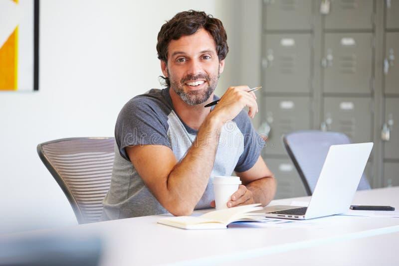 Homem ocasionalmente vestido que trabalha no estúdio do projeto fotografia de stock