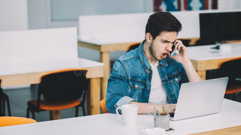 Homem ocupado novo com a barba que trabalha no portátil e que usa o telefone celular fotografia de stock