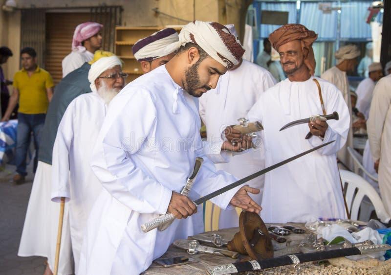 Homem omanense que compra uma espada fotos de stock