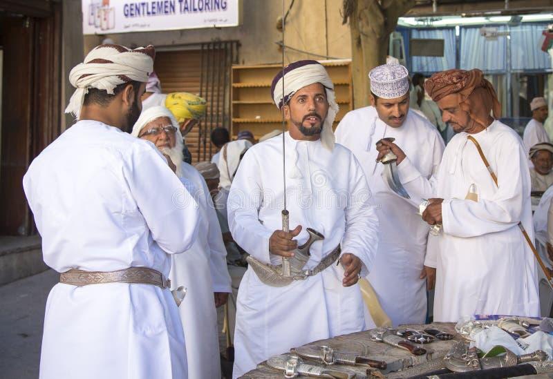 Homem omanense que compra uma espada imagens de stock