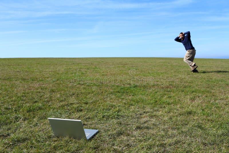 Homem oprimido que funciona no campo longe do portátil fotografia de stock