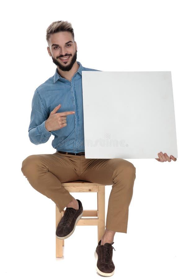 Homem orgulhoso assentado que aponta seu dedo para anular o quadro de avisos imagem de stock
