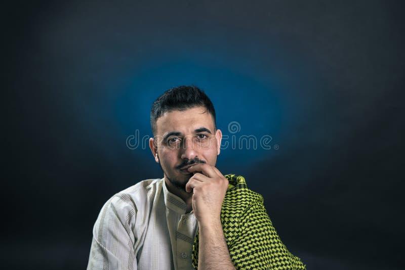 Homem oriental da aparência no vestido árabe nacional tradicional, com um olhar manhoso que guarda pensativamente os dedos a sua  fotografia de stock