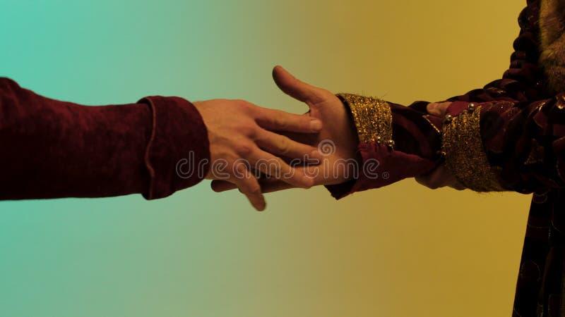 Homem oriental que toma uma parte de pepita de ouro de um outro homem, mãos isoladas no fundo colorido estoque Feche acima para fotografia de stock