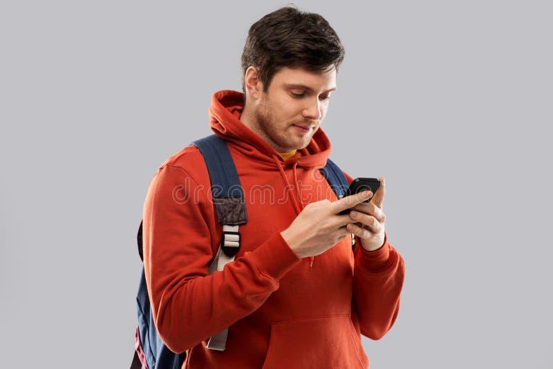 Homem ou estudante com o saco do smartphone e de escola imagem de stock