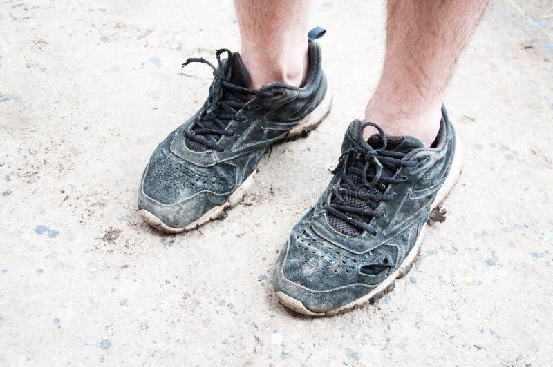 Homem ou mulher nas sapatilhas velhas e sujas brancas Sapatilhas rasgadas foto de stock