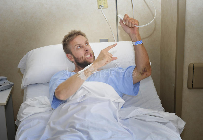 Homem paciente irritado na sala de hospital que encontra-se na cama que pressiona o sentimento do botão da chamada da enfermeira  foto de stock