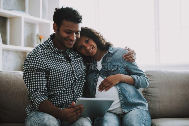 Homem paquistanês novo com a esposa grávida no sofá fotos de stock