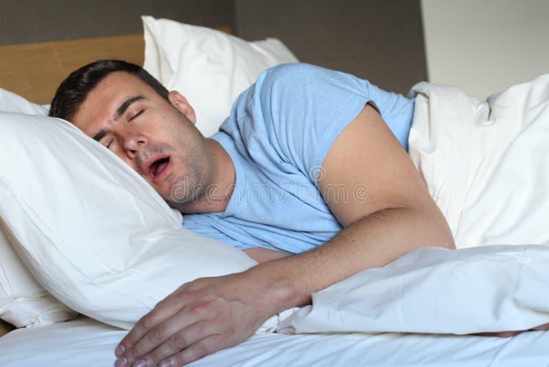 Homem para fora passado que baba na cama foto de stock