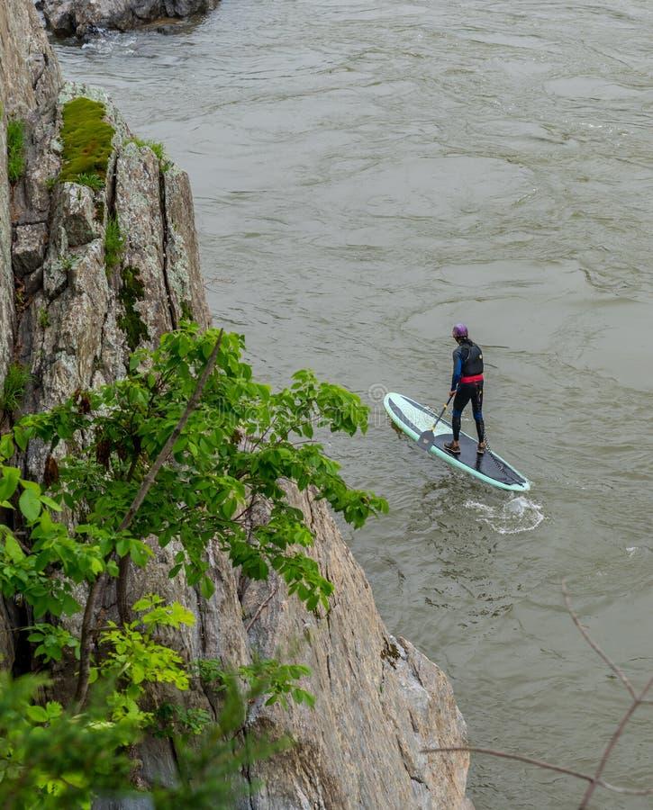 Homem parado em kayak e remando imagem de stock