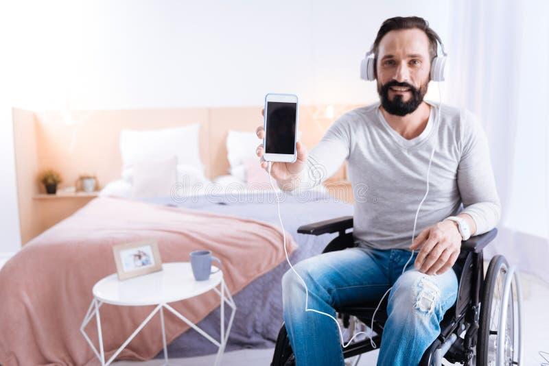 Homem paralizado exuberante que mostra seu telefone fotos de stock royalty free