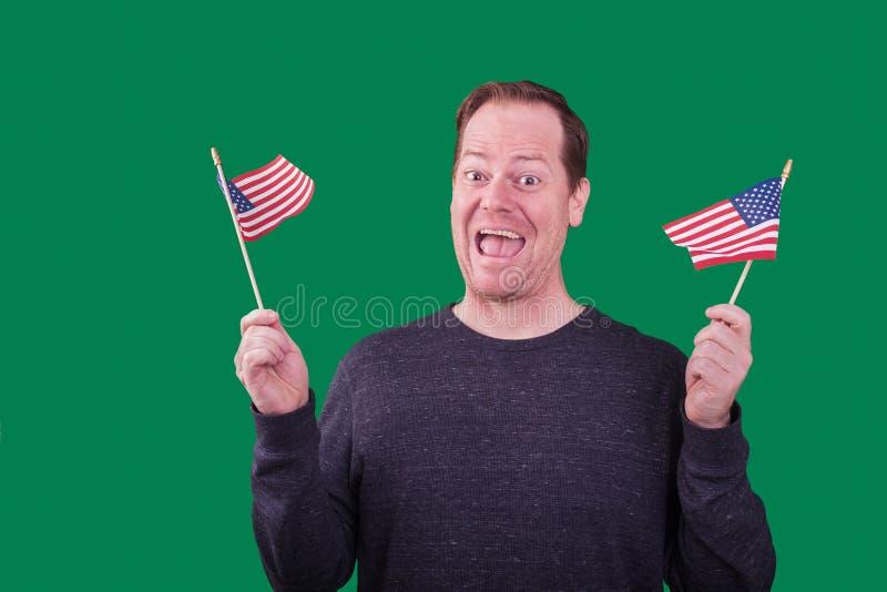 Homem patriótico que acena uma expressão facial feliz entusiasmado de duas bandeiras americanas no fundo de tela verde imagens de stock