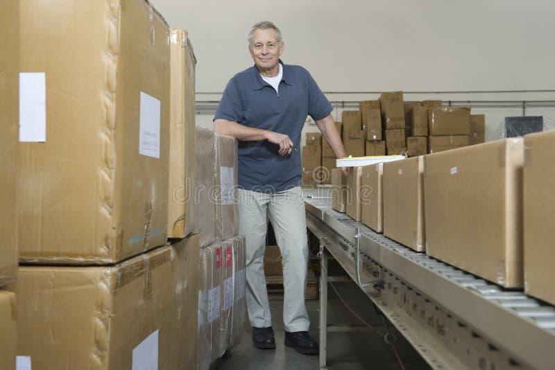 Homem pela correia transportadora e pelas caixas no armazém imagem de stock