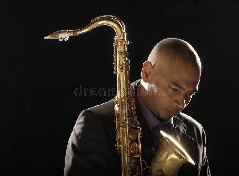 Homem pensativo com o saxofone que olha para baixo fotos de stock