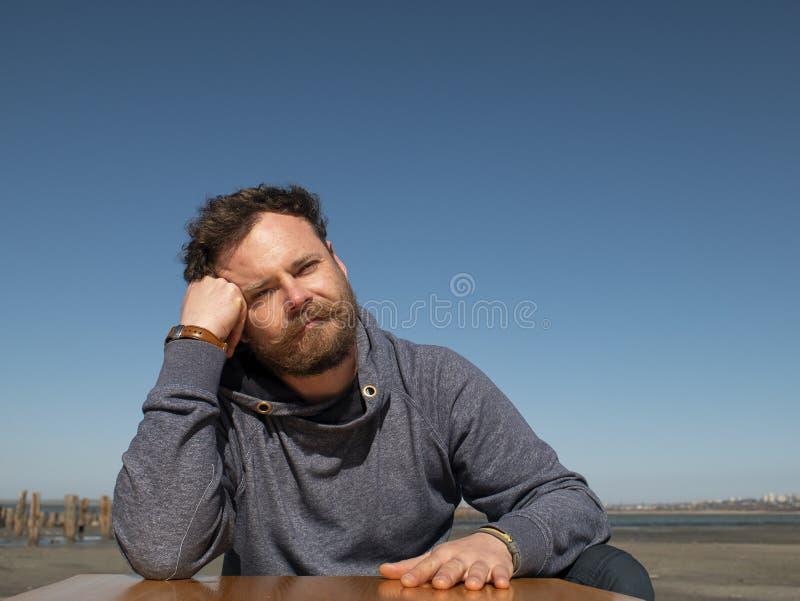Homem pensativo com uma barba e um bigode que sentam-se em uma mesa de centro contra um céu azul fotos de stock royalty free