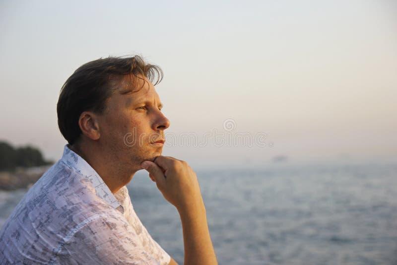 Homem pensativo considerável no mar imagens de stock