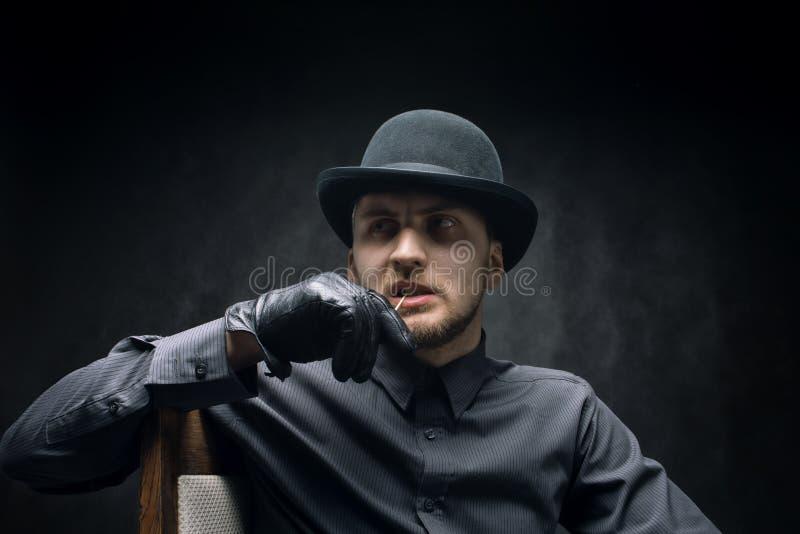 Homem pensativo em um chapéu e palito em sua boca, contra um fundo escuro fotos de stock royalty free
