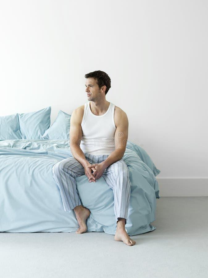 Homem pensativo no Nightwear que senta-se na cama fotos de stock