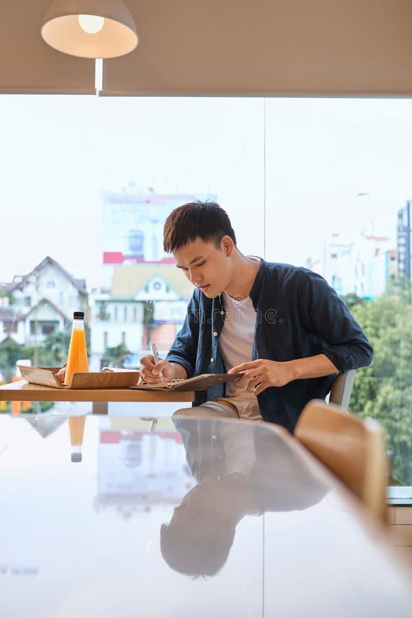 Homem pensativo que escreve ideias bem sucedidas novas para o artigo do blogue no interior do café imagens de stock royalty free