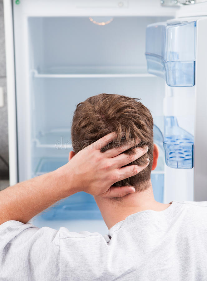 Homem pensativo que olha no refrigerador vazio imagens de stock