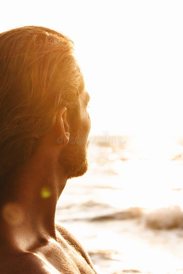Homem pensativo que olha o mar no por do sol foto de stock