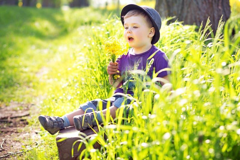 Homem pequeno bonito que senta-se na mala de viagem fotos de stock royalty free