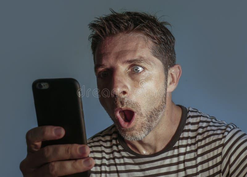 Homem perplexo e chocado novo que usa o telefone celular que olha meios sociais do Internet ou que verifica a notícia na descrenç fotos de stock royalty free