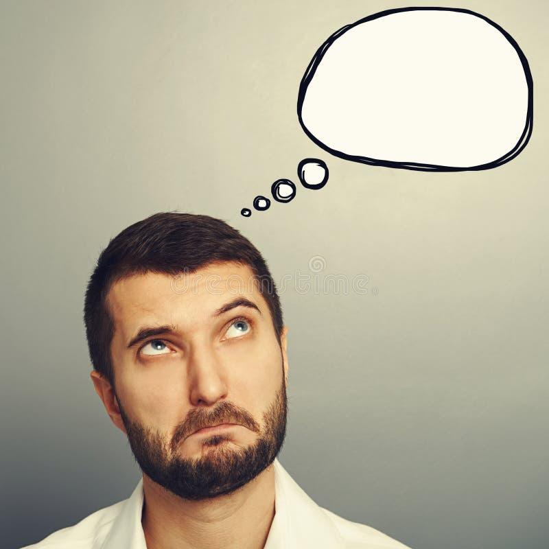 Homem perplexo que olha a bolha do discurso imagem de stock royalty free