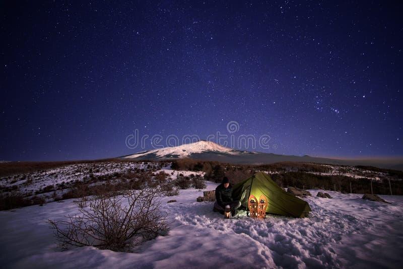 Homem perto da barraca iluminada na neve sob o céu estrelado imagem de stock