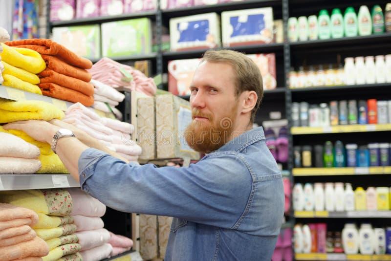 Homem perto do departamento com toalhas imagem de stock royalty free