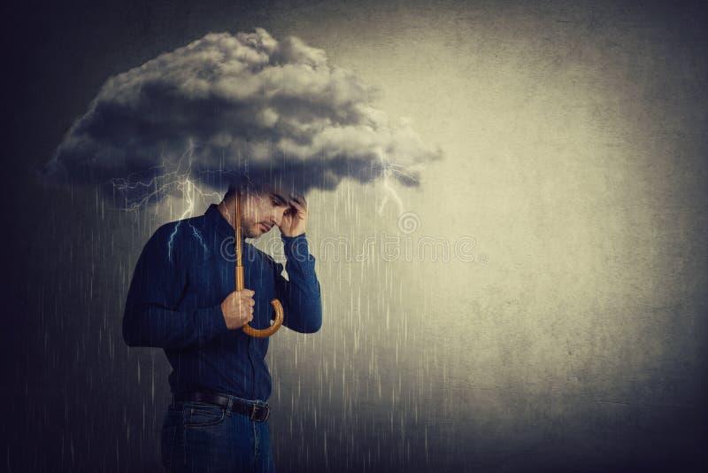 Homem pessimista, sob chuva, sofrendo ansiedade enquanto segurava uma nuvem de trovoada de guarda-chuva sobre a cabeça Conceito d fotografia de stock