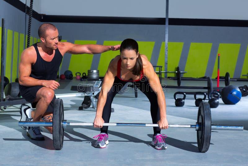 Homem pessoal do instrutor do Gym com a mulher da barra do levantamento de peso imagem de stock royalty free