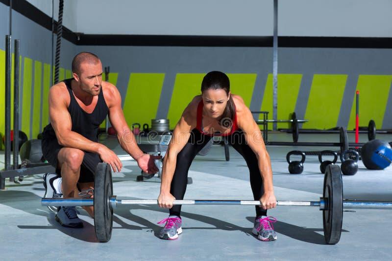 Homem pessoal do instrutor do Gym com a mulher da barra do levantamento de peso foto de stock