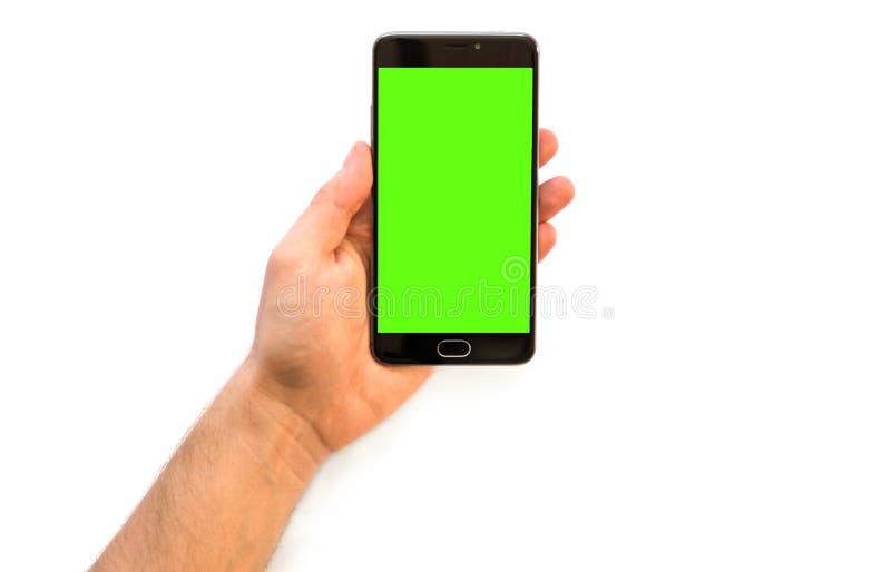 Homem plástico do cartão A dos pagamentos em linha que guarda um smartphone com a tela verde para os comp(s) da chave do croma imagem de stock