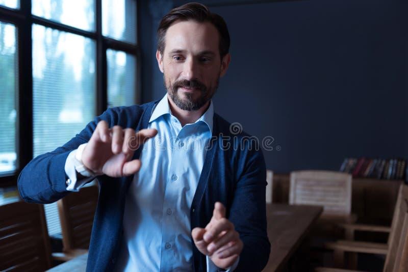 Homem positivo agradável que toca na tela virtual imagens de stock