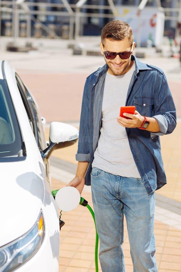 Homem positivo alegre que abastece seu carro foto de stock