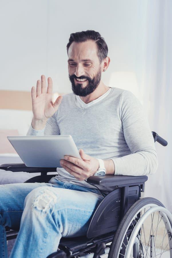 Homem positivo com inabilidade que sorri ao ter uma chamada video foto de stock royalty free