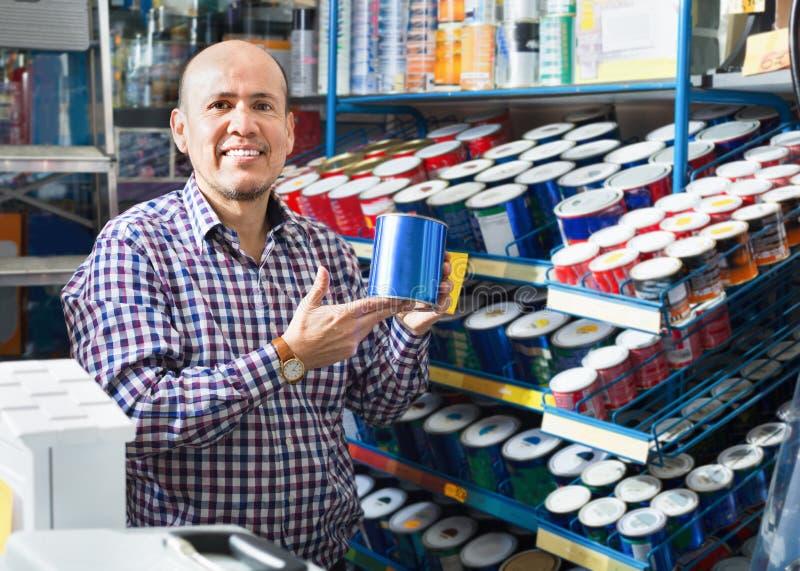 Homem positivo maduro que seleciona a pintura e a emulsão da parede na loja fotografia de stock