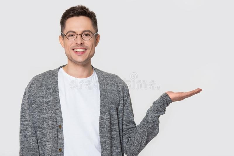Homem positivo nos vidros que mostram o copyspace vazio na palma aberta foto de stock royalty free