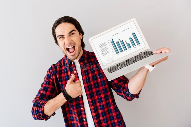 Homem positivo que guarda o portátil imagens de stock royalty free