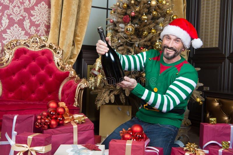 Homem positivo que ri ao sentar-se com a garrafa grande perto da árvore de Natal imagem de stock