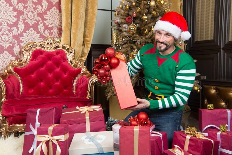Homem positivo que senta-se no assoalho e que mostra seus presentes do ano novo fotos de stock