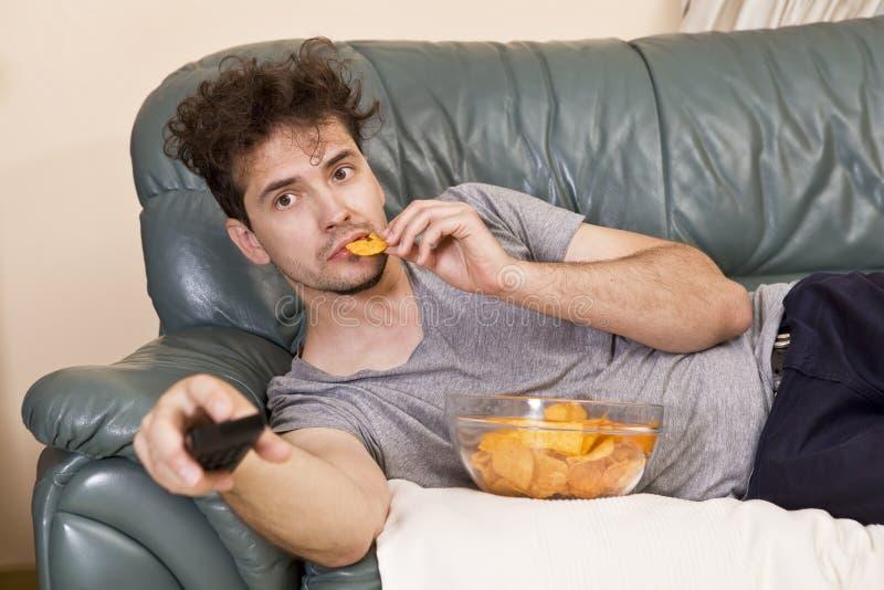 Homem preguiçoso com o telecontrole e microplaquetas no sofá imagem de stock royalty free