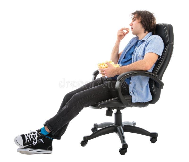 Homem preguiçoso que senta-se na poltrona que come o milho de PNF, isolado sobre o branco imagens de stock royalty free