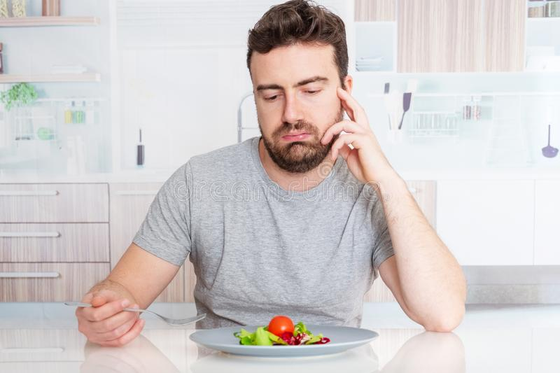 Homem preocupado com fome e morrido de fome com salada imagens de stock royalty free